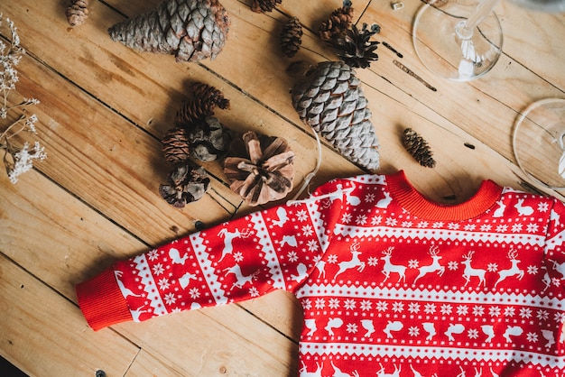Little red sweater with deers flatlay on wooden table near pine cones