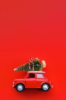 Маленькая красная машинка и рождественская елка на красном.