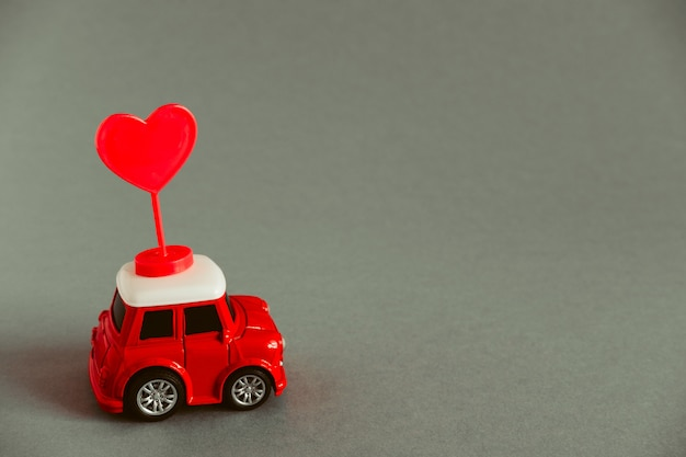 Little red toy car carries a red heart