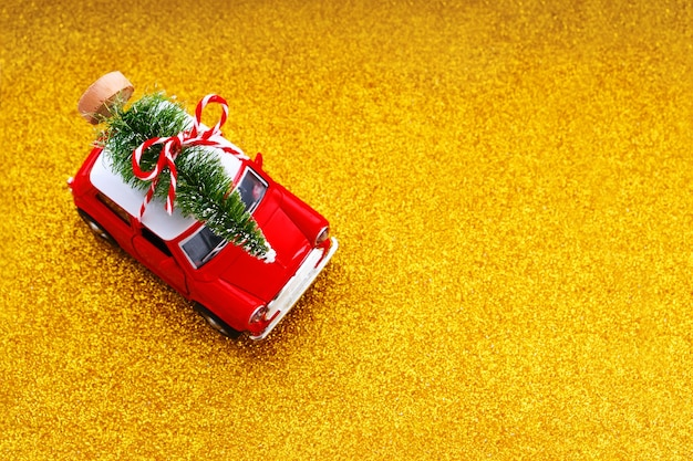 Little red toy car and christmas tree on glitter gold. top view