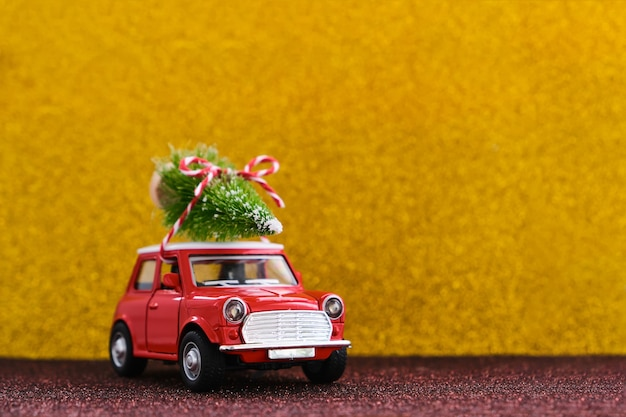 Little red toy car and christmas tree on glitter gold