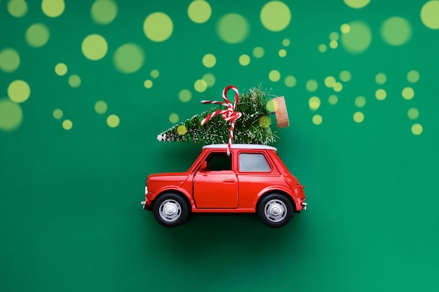 Little red toy car and christmas tree on green. top view