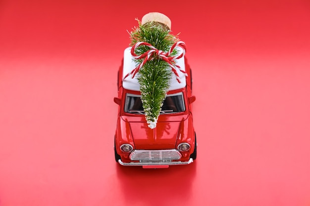 Little red toy car and christmas tree on red.