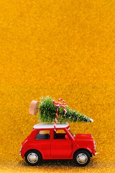 Little red toy car and christmas tree on a sparkle gold