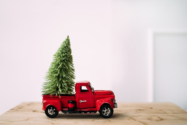 Little red toy car with green christmas tree on wooden and white background standing near the wall.