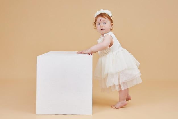 小さな赤毛の女の赤ちゃんがベージュの背景で遊んでいます。他のみんなのようではなく、額に大きなほくろ