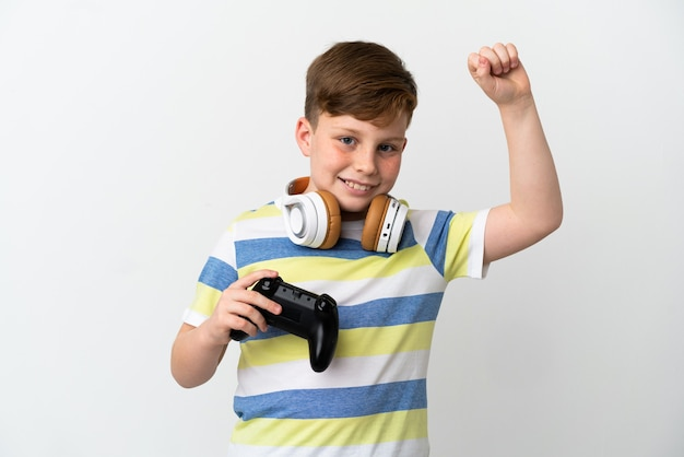勝利を祝う白い背景で隔離のゲームパッドを保持している小さな赤毛の少年