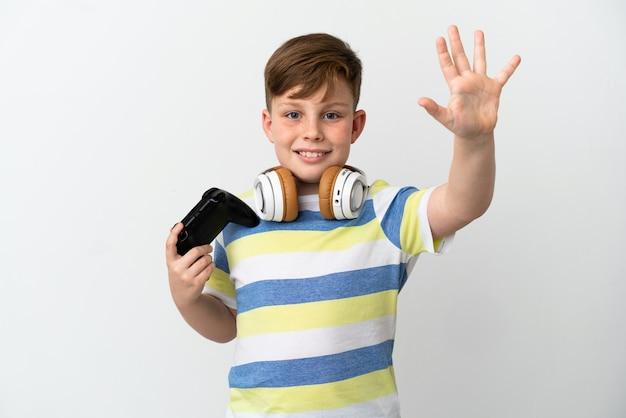 指で5を数える白い背景で隔離のゲームパッドを保持している小さな赤毛の少年