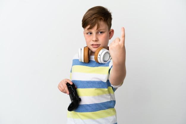 Маленький рыжий мальчик, держащий игровую площадку на белом фоне, делая приближающийся жест