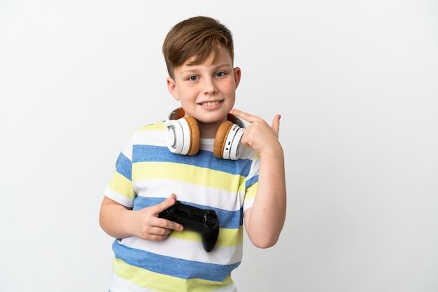 Маленький рыжий мальчик, держащий игровую площадку, изолированную на белом фоне, жестом показывает палец вверх
