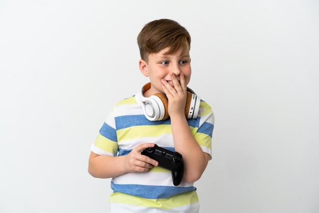 白い背景で隔離のゲームパッドを持って幸せで笑顔の小さな赤毛の少年が手で口を覆う