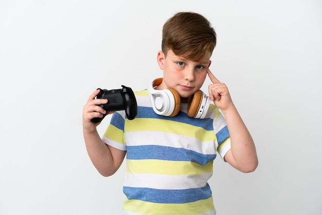 Маленький рыжий мальчик держит игровую площадку на белом фоне, сомневаясь и думая