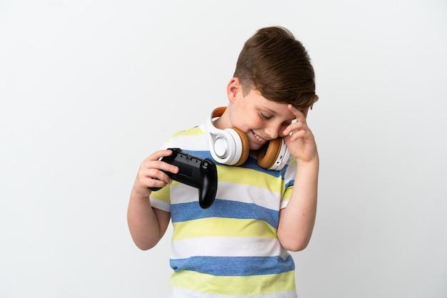 흰색 배경에 고립 된 게임 패드를 들고 웃는 빨간 머리 소년