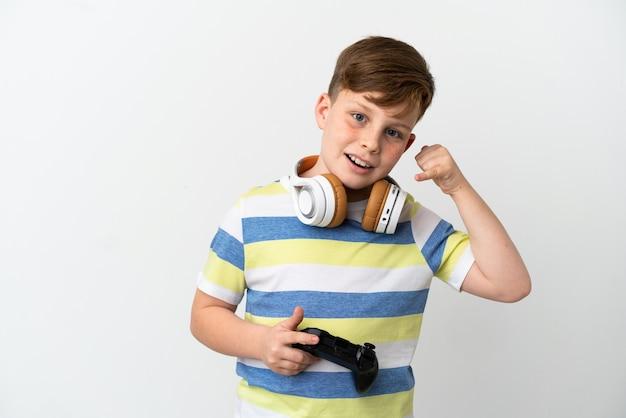 전화 제스처를 만드는 흰색 배경에 고립 된 게임 패드를 들고 작은 빨간 머리 소년. 다시 전화주세요 기호