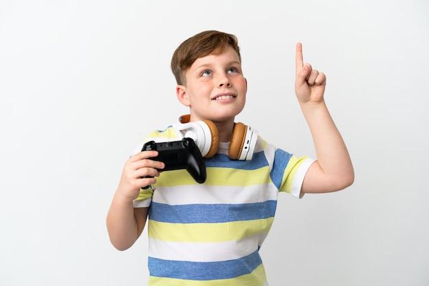 좋은 아이디어를 가리키는 흰색 배경에 고립 된 게임 패드를 들고 작은 빨간 머리 소년