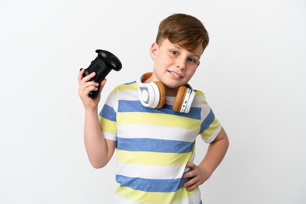 腰に腕を持ってポーズをとって笑って白い背景で隔離のゲームパッドを保持している小さな赤毛の少年