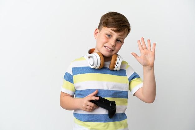 幸せな表情で手で敬礼する白い背景で隔離のゲームパッドを保持している小さな赤毛の少年