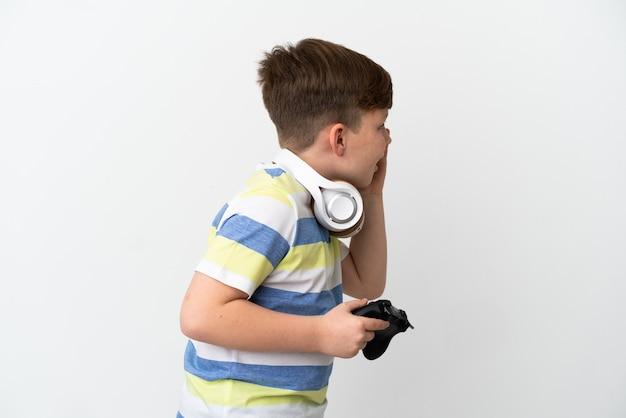横に大きく開いた口で叫んで白い背景で隔離のゲームパッドを保持している小さな赤毛の少年