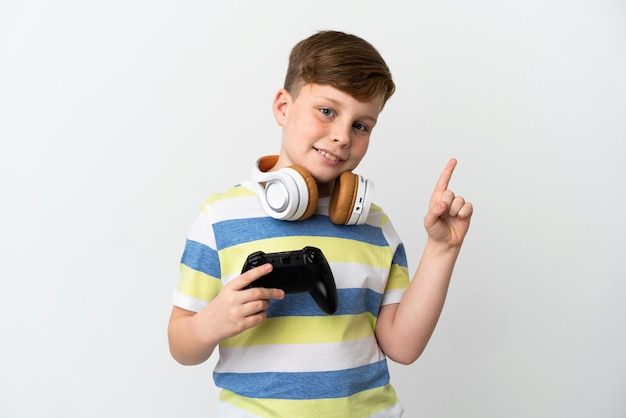 白い背景で隔離のゲームパッドを持って、最高のサインで指を見せて持ち上げる小さな赤毛の少年