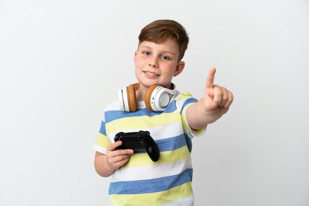 白い背景で隔離のゲームパッドを持って指を見せて持ち上げる小さな赤毛の少年