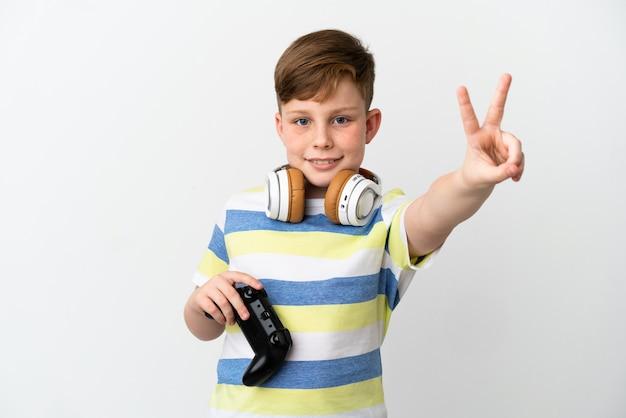 笑顔と勝利のサインを示す白い背景で隔離のゲームパッドを保持している小さな赤毛の少年