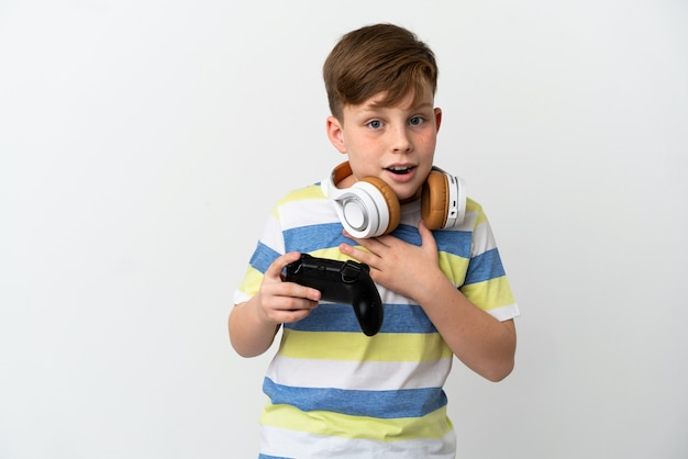 흰색 배경에 격리된 게임 패드를 들고 있는 빨간 머리 소년은 오른쪽을 바라보면서 놀라고 충격을 받았습니다.