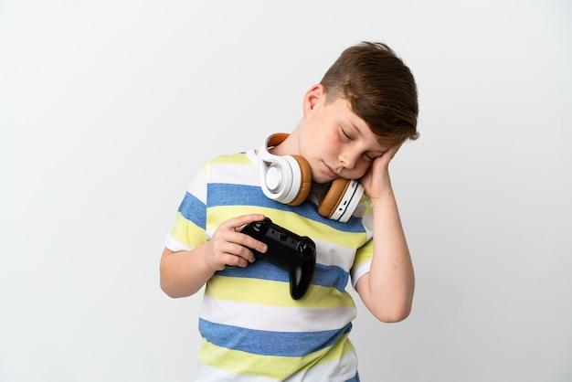 흰색 배경에 두통이 있는 게임 패드를 들고 있는 빨간 머리 소년
