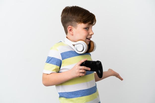 흰색 배경에 격리된 게임 패드를 들고 있는 빨간 머리 소년은 측면을 바라보면서 놀란 표정을 짓고 있습니다.
