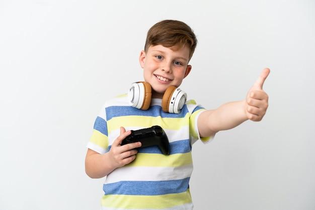 좋은 일이 일어났기 때문에 엄지손가락으로 흰색 배경에 격리된 게임 패드를 들고 있는 어린 빨간 머리 소년