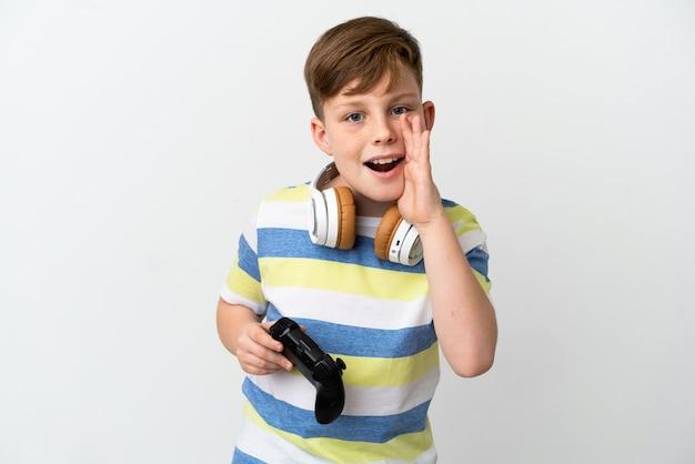 口を大きく開いて叫んで白い表面に分離されたゲームパッドを保持している小さな赤毛の少年