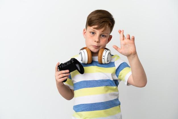 指が交差し、最高を願って白い表面に分離されたゲームパッドを保持している小さな赤毛の少年