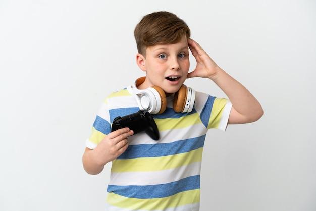 驚きの表情で白い表面に分離されたゲームパッドを保持している小さな赤毛の少年