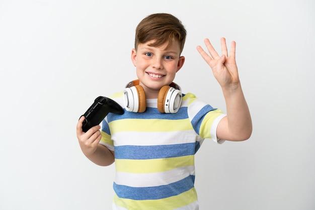 幸せな白い壁に分離されたゲームパッドを保持し、指で4を数える小さな赤毛の少年