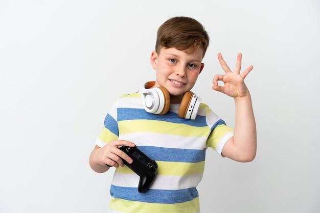 指でokサインを示す白い壁に分離されたゲームパッドを保持している小さな赤毛の少年