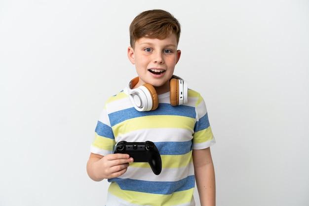 驚きの表情で白い壁に分離されたゲームパッドを保持している小さな赤毛の少年