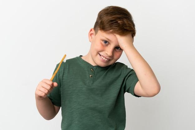 흰색 배경에 격리된 칫솔을 들고 있는 어린 빨간 머리 소년은 무언가를 깨닫고 해결책을 모색하고 있습니다