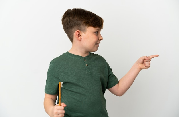 製品を提示する側を指している白い背景で隔離の歯ブラシを保持している小さな赤毛の少年