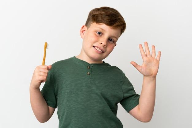 Маленький рыжий мальчик держит зубную щетку на белом фоне, салютуя рукой с счастливым выражением лица