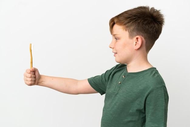 Маленький рыжий мальчик держит зубную щетку на белом фоне с счастливым выражением лица
