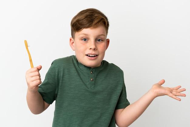 Маленький рыжий мальчик держит зубную щетку на белом фоне с шокированным выражением лица