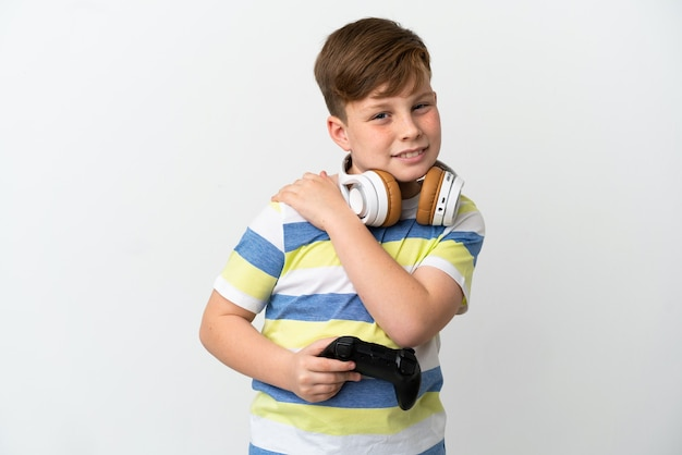 Little redhead boy holding a game pad isolated on white wall suffering from pain in shoulder for having made an effort