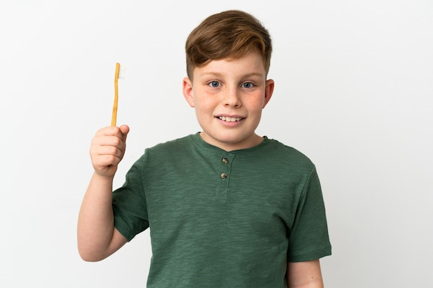 Little redhead boy holding a toothbrush isolated on white background with surprise and shocked facial expression
