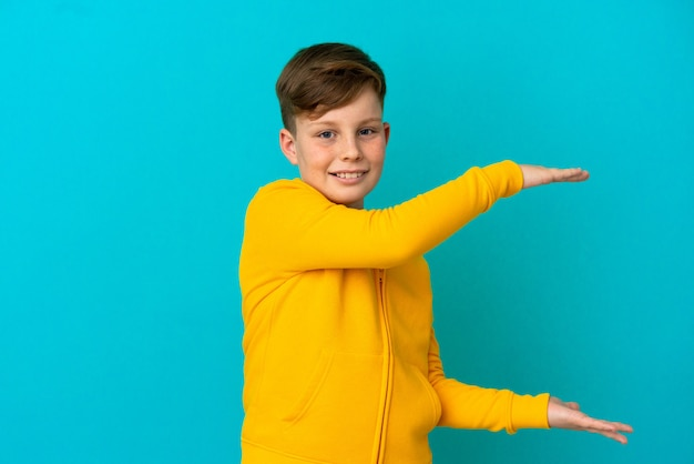 Little redhead boy isolated on blue background holding copyspace to insert an ad