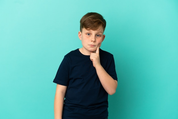 Little redhead boy isolated on blue background and thinking