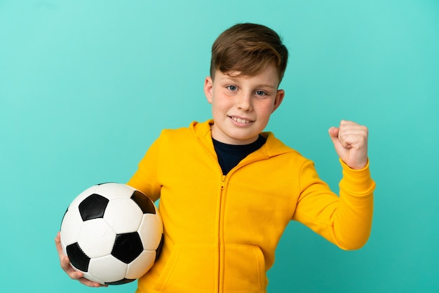 Little redhead boy isolated on blue background with soccer ball celebrating a victory