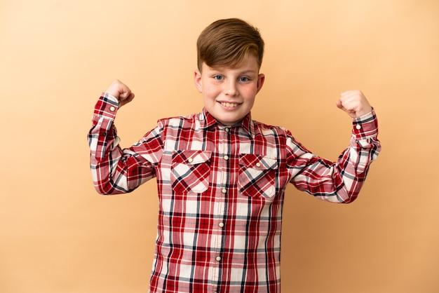 승리를 축 하 하는 베이지색 배경에 고립 된 작은 빨간 머리 소년