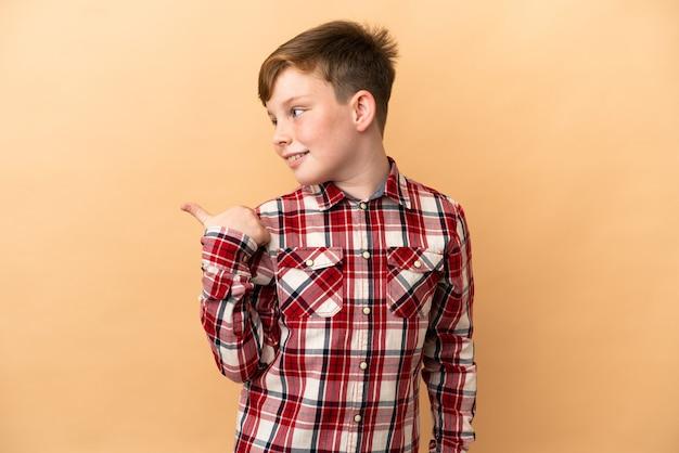 제품을 제시하기 위해 측면을 가리키는 베이지색 배경에 격리된 작은 빨간 머리 소년