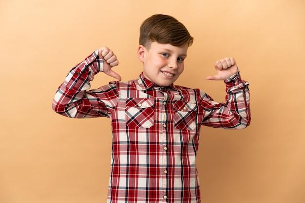 Маленький рыжий мальчик, изолированные на бежевом фоне, гордый и самодовольный