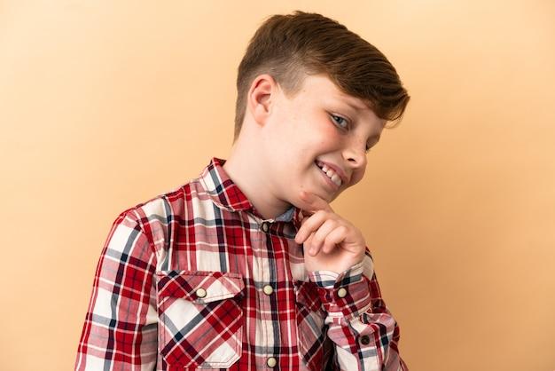베이지색 배경에 고립 된 작은 빨간 머리 소년