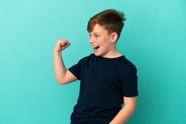 승리를 축하하는 파란색 배경에 고립 된 작은 빨간 머리 소년